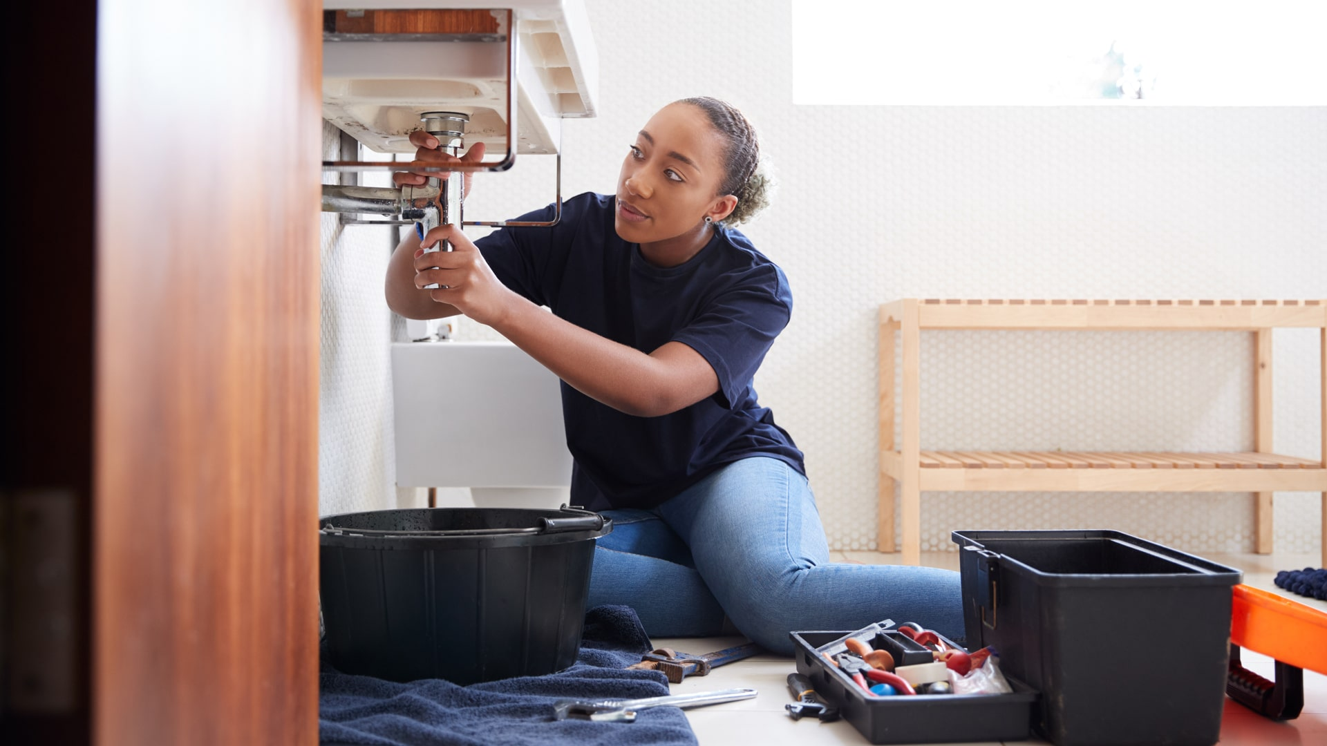 Female plumber working to fix leaking sink in home