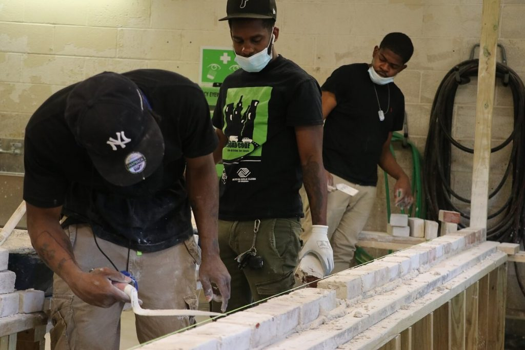 Students undergoing hands-on construction training in construction school