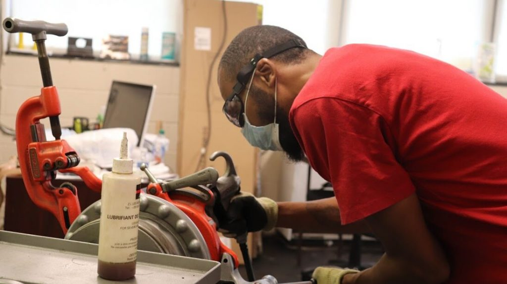 student getting plumbing training in a skilled trade program