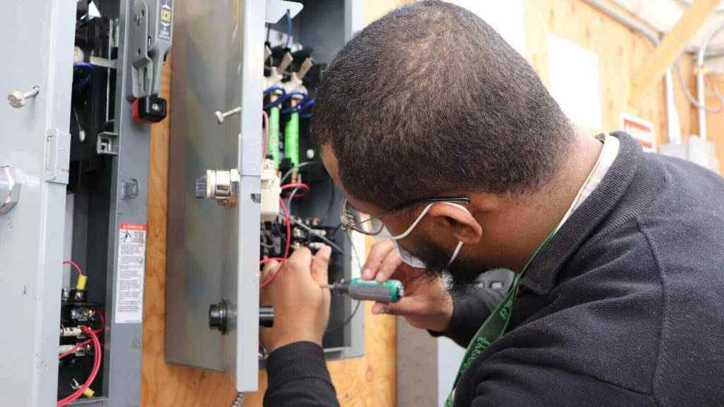 Student training to become an electrician through electrician program in trade school