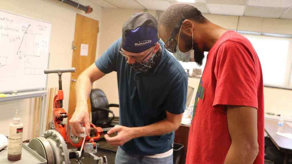 Teacher and student in the plumbing trade school